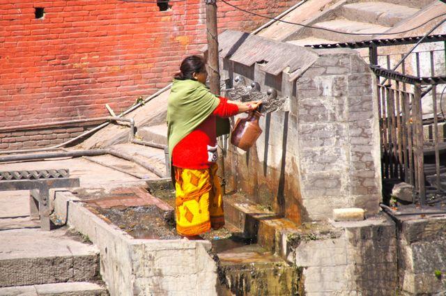 A woman getting water along the Bagmati.