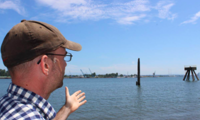 Dan Serres points out fossil fuel infrastructure along the Columbia River in Portland, Oregon, July 16, 2018. Thomson Reuters Foundation/Gregory Scruggs